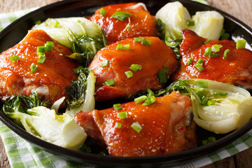 Delicious fried chicken thighs with bok choy and green onions close-up. horizontal