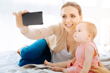 Delighted woman taking photos with her daughter