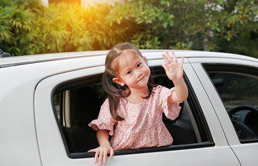 Adorable asian little girl in car smiling and looking camera sitting on a backseat of a car waving goodbye.