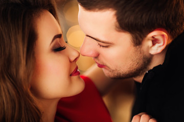 Close-up of beautiful couple kissing against blurred light bokeh