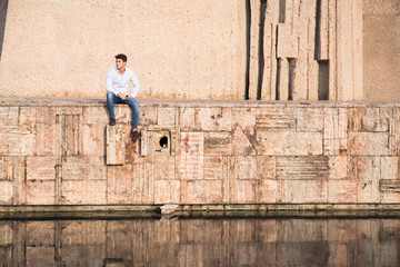 Young man in shirt sitting on beige wall over water on sunny day.