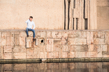 Young man sitting on wall over water and speaking on phone on sunny day.