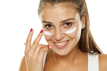 young woman applying cream to her face
