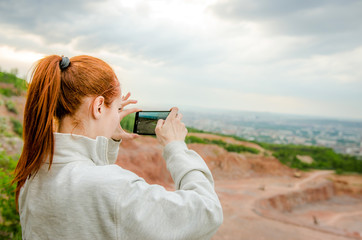 Side view of ginger woman making photo on smartphone