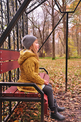 Little cute girl sitting on the bench