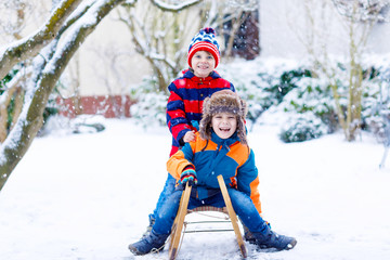 Two little kid boys enjoying sleigh ride in winter