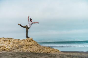 Man balancing on stone at sea
