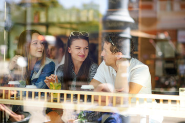 Three young friends behind glass of cafe.