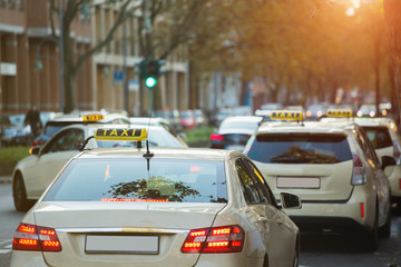Taxi cars on the city street.  Cars parked at the side of the road.