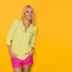 Smiling Beautiful Blond Woman In Yellow Shirt And Pink Shorts