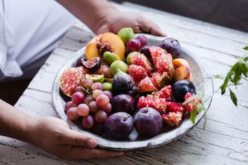 Person serving tray full of fresh seasonal fruits