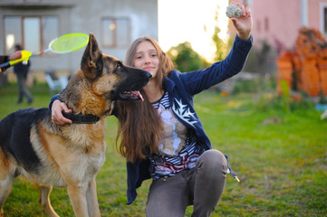 The girl educates her dog a German shepherd