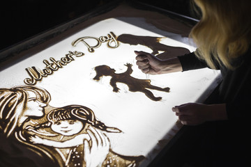 The woman draws on sand animation for mother's day