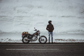 Man with motorcycle in snowy road