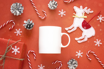 White coffee mug  with Christmas decorations on red background. Space for text or design.