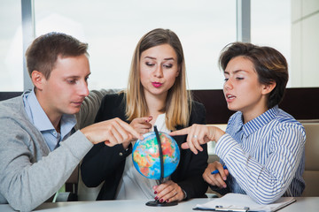 Business people hold little office globe and point at it. Searching for a country to travel. Vacation concept. Group of young students study globe