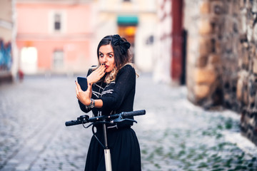 Funky woman making faces while looking at camera. Young woman taking photographs with smartphone