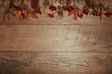 Autumn arrangement of colorful leaves and autumn flowers on a wooden background with free space for text. Top view, season concept, toned retro effect, flat lay