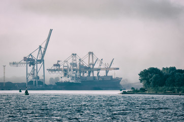 SHIP IN A SEA PORT - Transshipment terminal in the mist