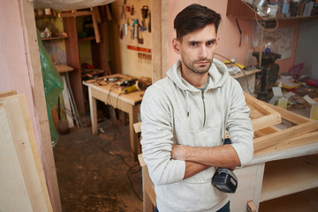 Portrait of a guy working in a home workshop.