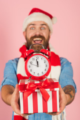 Christmas present box and alarm clock in blurred man hands