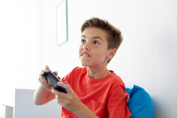 happy boy with gamepad playing video game at home