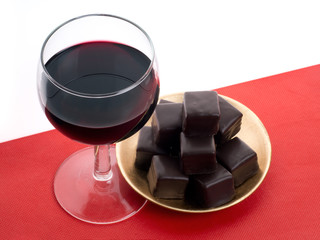 Red wine and dark chocolates on red cloth. With copy space.