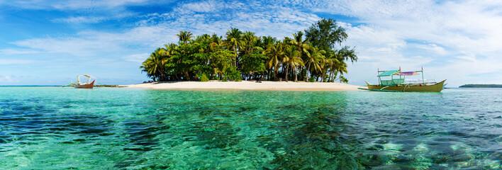 Tropical Guyam Island with traditional fishing boats
