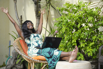 happy black afro american woman in elegant dress working on luxury terrace villa with laptop excited and happy