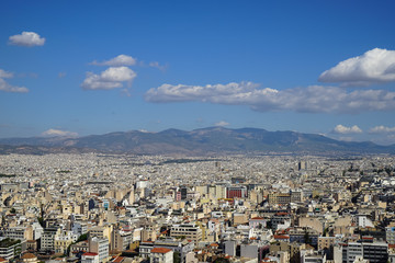 View of beautiful Athens city from Acropolis showing white buildings architecture, mountain, trees, blue sky and floating white cloud background