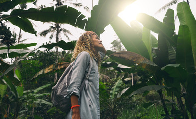 View from the bottom photo of a beautiful caucasian female with curly hair standing amid the huge green leaves and impressed with wild tropical nature during journey through the jungles.