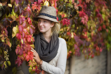 Portrait of a beautiful young girl against the background of autumn leaves