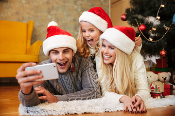 Funny beautiful family in Santa's hat taking selfie on mobile phone while lying on the floor near Christmas tree