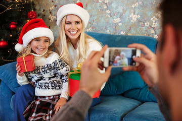 Cropped view of father taking photo of his smiling wife and daughter in Santa's hat, selective focus