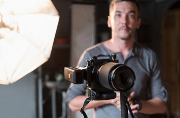 close-up of the camera on the background of the photographer and lighting equipment