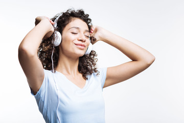 Curly-haired woman listening to music in headphones