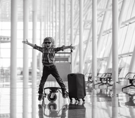 Happy kid with luggage  in airport terminal.  Travel concept. Child with bag ready for holiday. Vacation in Portugal.