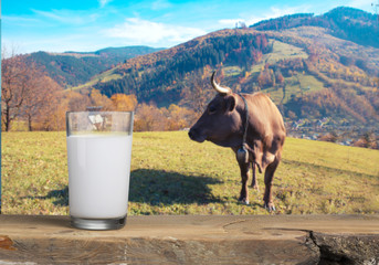 A bottle of milk and glass of milk on a wooden table on a blue background