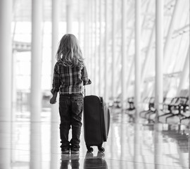 Little kid with luggage  in airport terminal. Back view.  Happy travel concept. Child with bag ready for holiday. Vacation in Portugal.