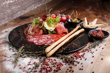 Traditional meat plate italian snack on wooden table with dressing
