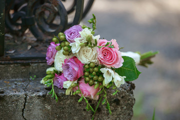 Roses and berries bridal bouquet positioned on a rustic, old iron fence under overcast light with blurred background