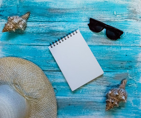 Bright background with painted blue, blue paint boards, sunglasses, straw hat, an open notebook  and seashells. Top view
