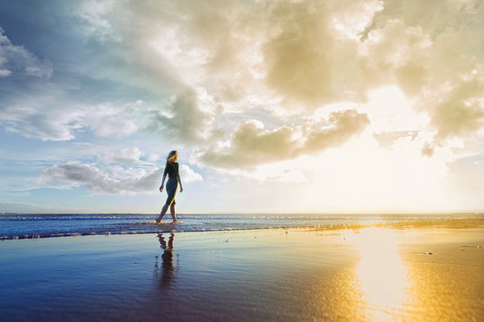 Young woman walking on the beach at sunset. Sky is cloudy and beautiful.