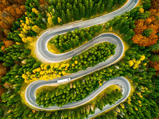 Lorry winding up its way on a curvy road through autumn colored