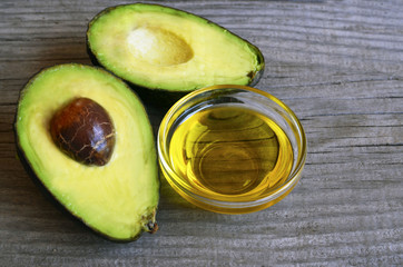 Avocado oil in a glass bowl and fresh organic avocado on old wooden background.Healthy eating,diet,body care concept.