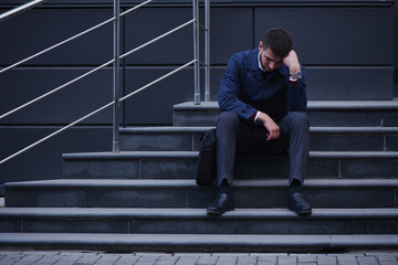 The concept of the bankruptcy of a business man sitting on stairs on the street holding his head