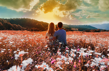 Young couple sitting on the chamomiles field and enjoying sunset in mountains.