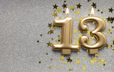 Number 13 gold celebration candle on star and glitter background