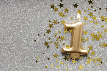 Number 1 gold celebration candle on star and glitter background