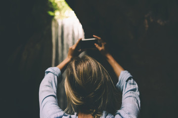 View from the back photo of blonde female taking photo of an outstanding beautiful waterfall by the camera of her mobile phone in the depth of tropical jungles during summer vacation.